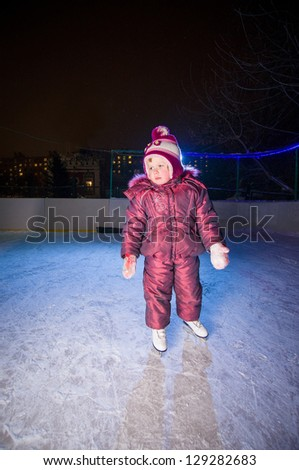 Adorable girl in skates stay on ice rink in evening - stock photo
