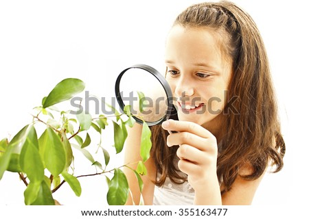 Adorable girl looking at a plant through a magnifying glass. Isolated on white background - stock photo