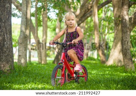 Adorable girl on bicycle in park on grass under trees - stock photo