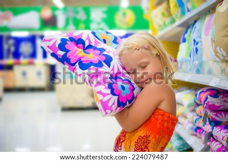 Adorable girl play with pillow, imitating sleep in department section - stock photo