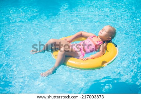 Adorable girl relax on yellow life ring in pool at tropical beach resort - stock photo