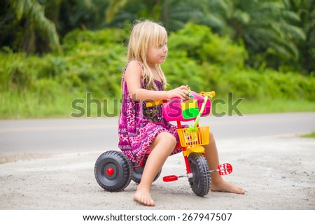 Adorable girl ride on tricycle with toy doll - stock photo