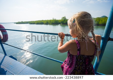 Adorable girl see out to water on upper deck of ferry boat between islands - stock photo