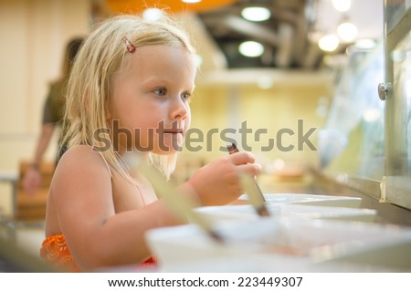 Adorable girl select dishes under shopping window on food court in mall - stock photo