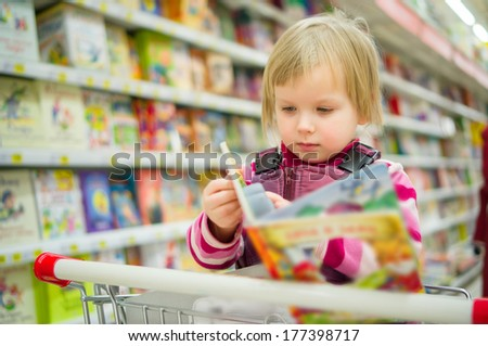 Adorable girl sit on shopping cart with kids book in supermarket - stock photo