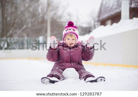 Adorable girl skate on ice rink, seat on ice covered with snow after fall and play with snow - stock photo