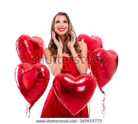 Adorable girl surrounded by red hearts looking up - stock photo
