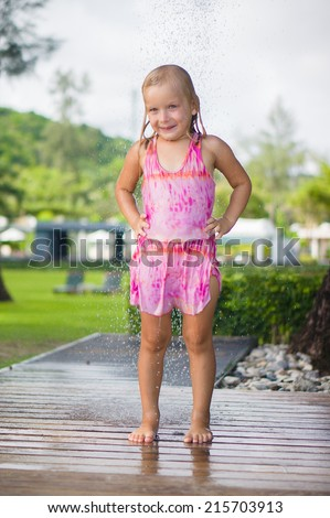 Adorable girl take shower under tree at tropical beach resort - stock photo