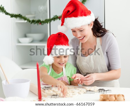Adorable girl with her mother baking Christmas cookies in the kitchen - stock photo