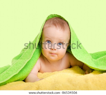 Adorable happy baby in colorful towel - stock photo