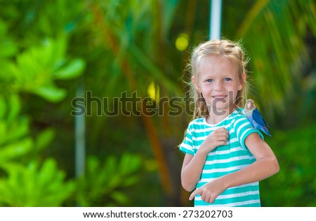 Adorable happy girl at beach with colorful little bird - stock photo