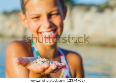 Adorable happy girl holding crab on hand on the beach. Focus on the crab. - stock photo