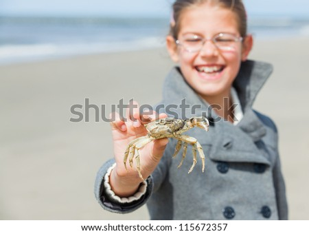 Adorable happy girl holding crab on the beach on spring day. Focus on the crab. - stock photo