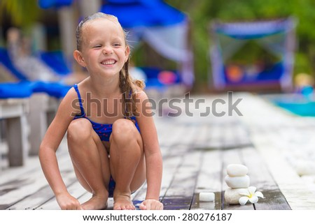 Adorable happy girl near swimming pool - stock photo