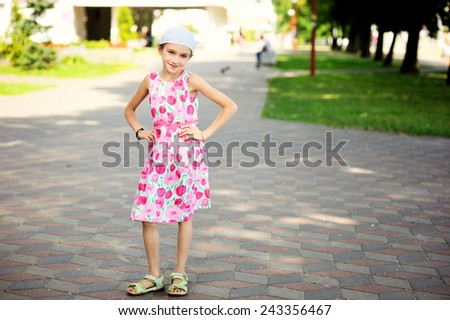 Adorable happy girl with brunette hair wearing a summer dress enjoying walk in the city - stock photo
