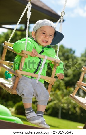 Adorable happy kid swinging outdoors  - stock photo