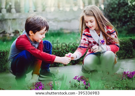 Adorable happy kids outdoors on spring day in beautiful blooming garden - stock photo