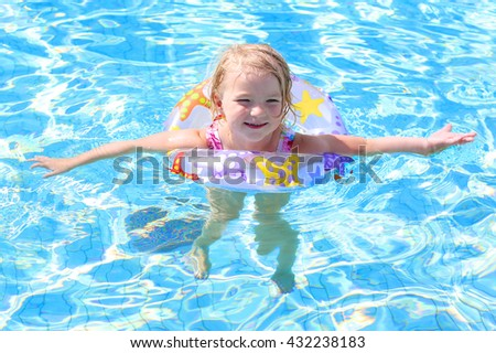 Adorable happy little child, curly toddler girl in swimming suit having fun relaxing and floating on an inflatable toy ring in a pool on sunny day during summer vacation in resort - stock photo