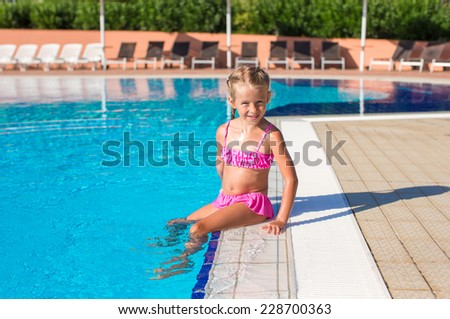 Adorable happy little girl in the swimming pool outside - stock photo