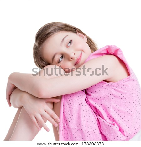 Adorable happy little girl sitting on the bed and looking up -  isolated on white. - stock photo