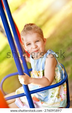 Adorable happy little girl smiling on swing on a sunny summer playground in a park.  - stock photo