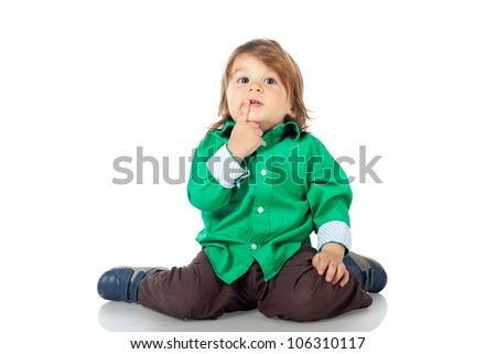Adorable happy little kid, 2 years old boy, sitting on the floor gesturing a kiss or a secret, wearing shirt and jeans. High resolution image isolated on white background with copy space. Studio shot. - stock photo