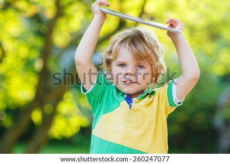 Adorable happy little toddler boy holding tablet pc, outdoors. Child learning with modern technology. - stock photo