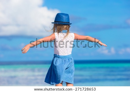 Adorable happy smiling little girl in hat on beach vacation - stock photo