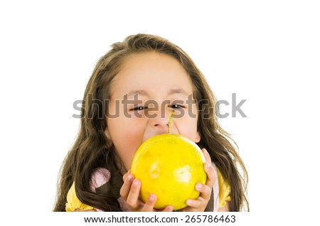 Adorable healthy little girl eating a passionfruit in front of her face isolated on white - stock photo