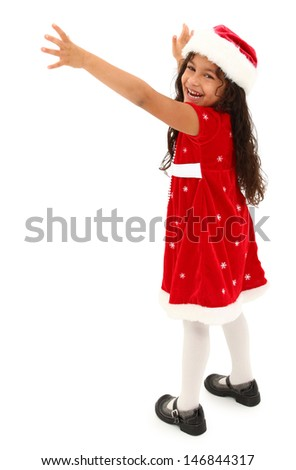 Adorable hispanic preschooler reaching out. Wearing christmas dress and hat. Clipping path. - stock photo