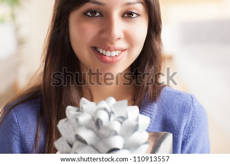 Adorable Hispanic woman wrapping gift with silver wrapping paper and silver bow in living room at table wearing blue shirt. - stock photo