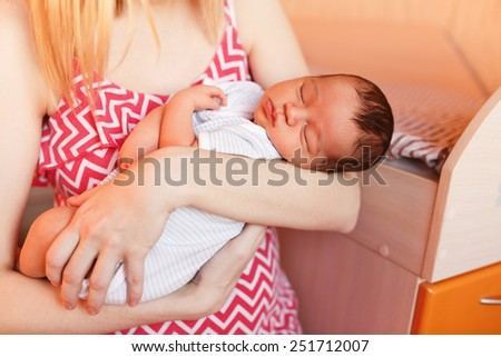 Adorable infant baby in the arms of my mother, close-up - stock photo