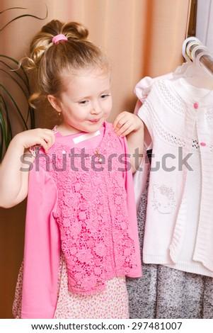 Adorable joyful little girl choosing dress - stock photo