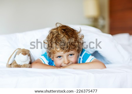 Adorable kid boy after sleeping in his white bed with toy. - stock photo