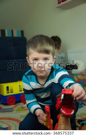 Adorable kid boy playing with cars and toys at home - stock photo