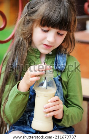 Adorable kid girl drinking milk coctail outdoors in the garden - stock photo