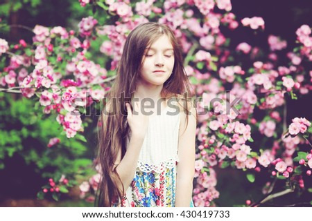 Adorable kid girl in blooming apple garden on beautiful spring day - stock photo