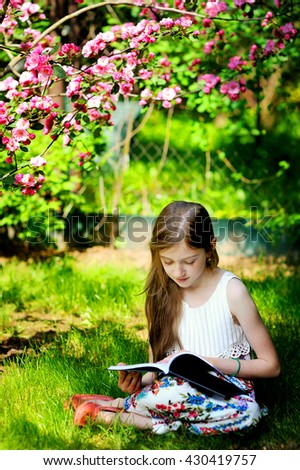 Adorable kid girl in blooming apple garden on beautiful spring day reading book - stock photo
