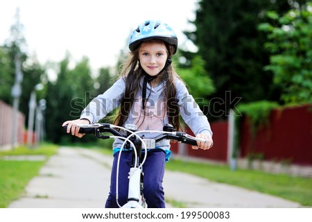 Adorable kid girl in blue helmet riding her bike  - stock photo