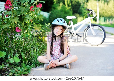 Adorable kid girl in blue helmet sitting on the road in front of her bike in the lovely sunny summer evening - stock photo