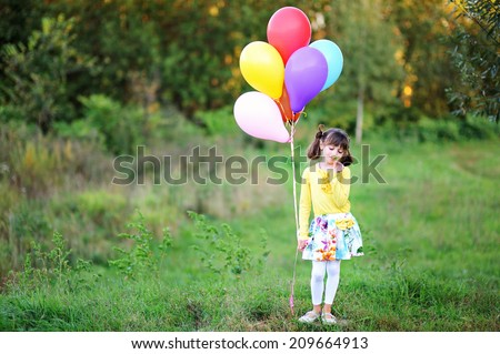 Adorable kid girl in colorful fashion outfit run  with bunch of colorful balloons in the field at the warm autumn day - stock photo