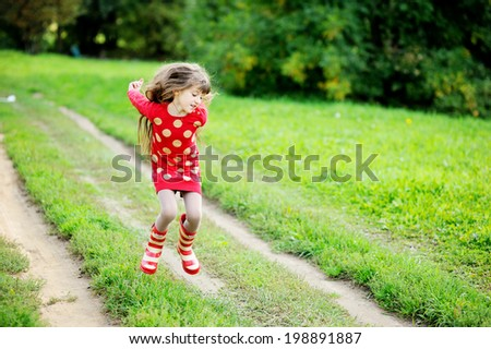 Adorable kid girl in red sweater dress and stripe rainboots jumping and having fun outdoors in the sunny autumn day - stock photo