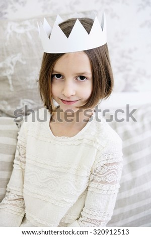 Adorable kid girl in white dress and paper crown - stock photo