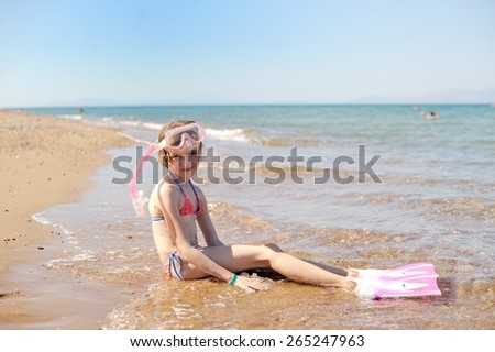 Adorable kid girl with mask on the beach - stock photo
