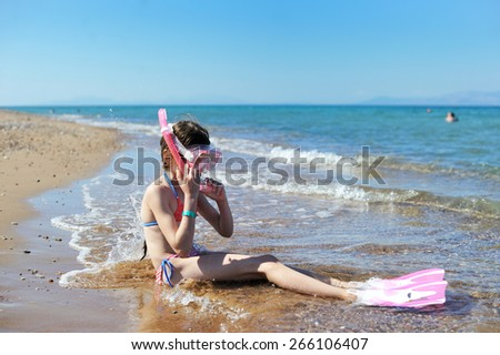 Adorable kid girl with mask on tne beach - stock photo