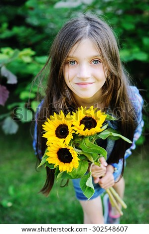 Adorable kid girl with sunflowers outdoor - stock photo