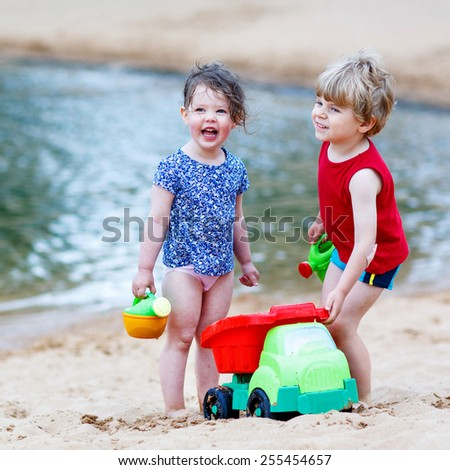 Adorable kids, two siblings, girl and boy having fun and playing together with sand toys near city lake on hot summer day. Active outdoors leisure with kids in summer, on sunny day. - stock photo