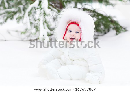 Adorable laughing baby sitting in snow under a Christmas tree - stock photo