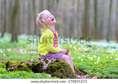 Adorable laughing child, blonde healthy toddler girl enjoying nature, playing and hiking in spring forest, picking, touching and holding white snowdrops flowers - stock photo