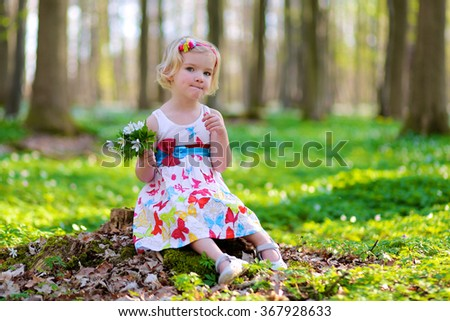Adorable laughing child, blonde healthy toddler girl enjoying nature, playing and hiking in spring forest, picking, touching and holding snowdrops flowers - stock photo